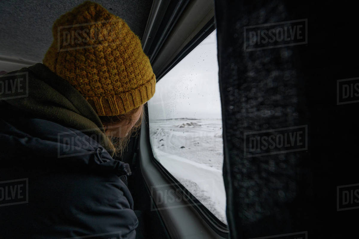 Woman wearing a woolly hat looking out of the window of a campervan at the sea. Winter Surfing Royalty-free stock photo