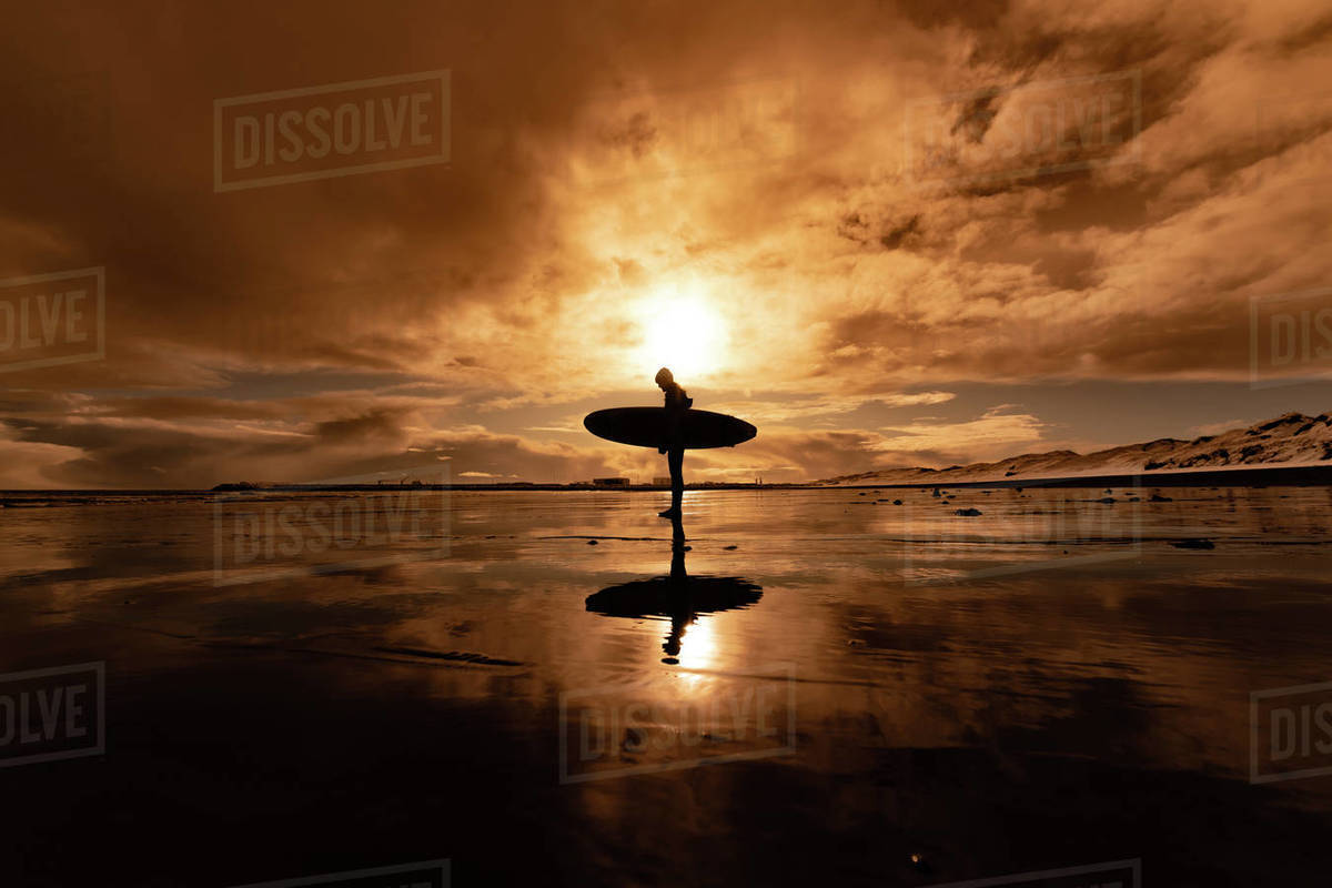 Silhouette of a woman carrying a surfboard walking across a beach with a sunset in the background. Royalty-free stock photo