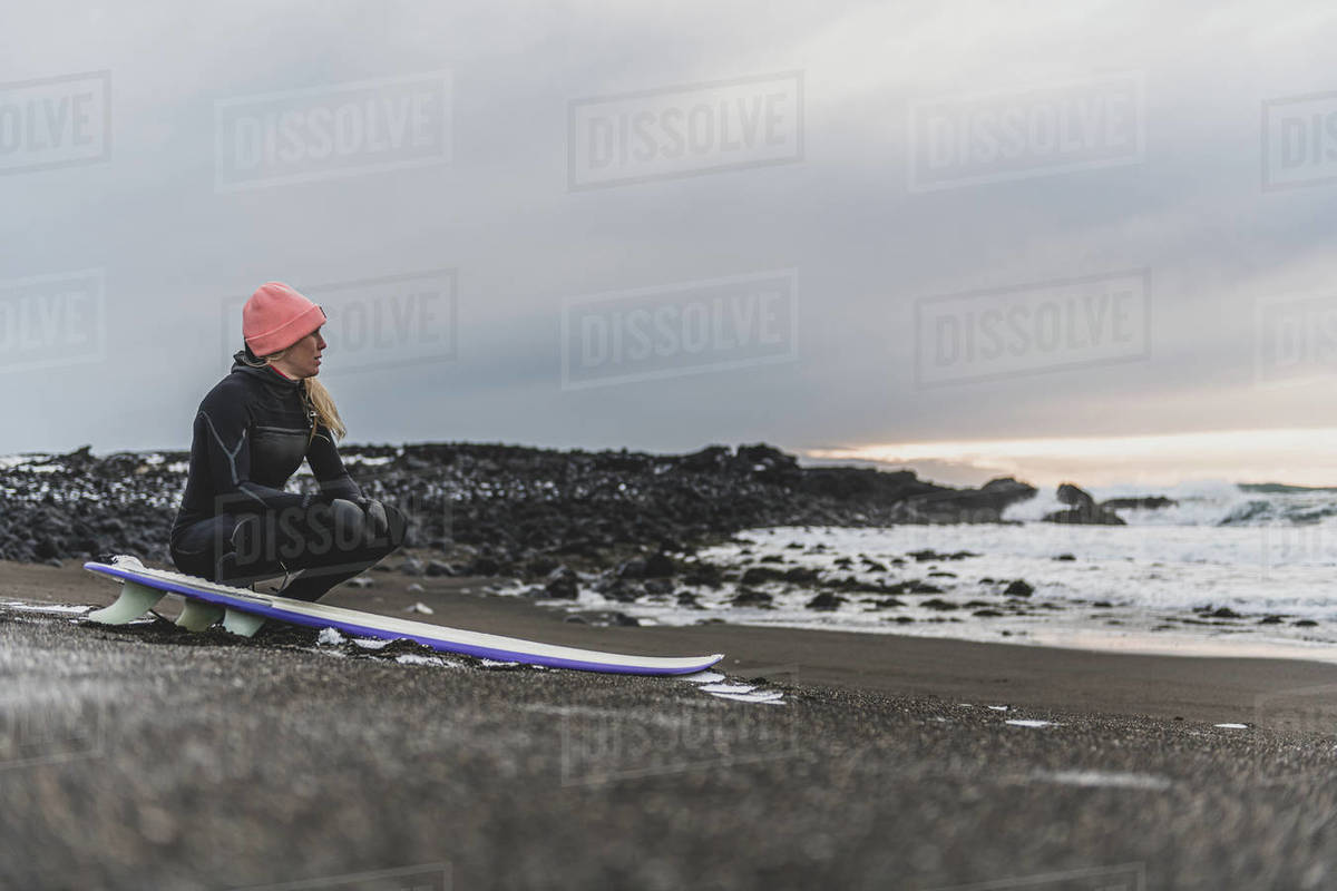 A woman sitting on her surfboard on a beach looking out to sea. Royalty-free stock photo