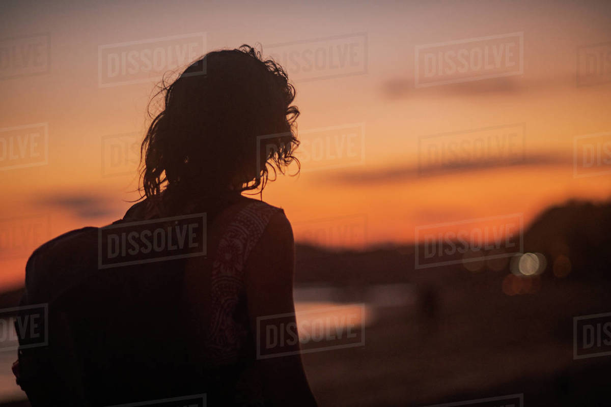 Silhouette of a young person with a backpack on a beach at sunset. Royalty-free stock photo