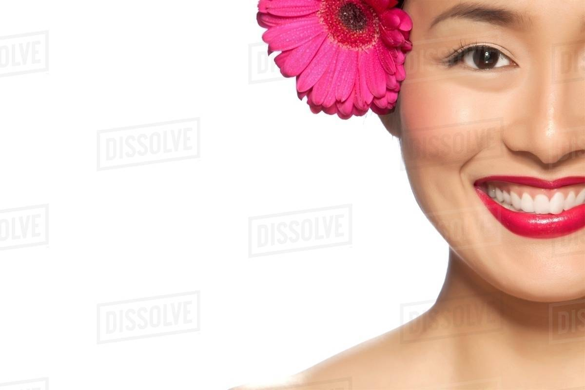 Young Woman Wearing Pink Flower In Hair Against White Background