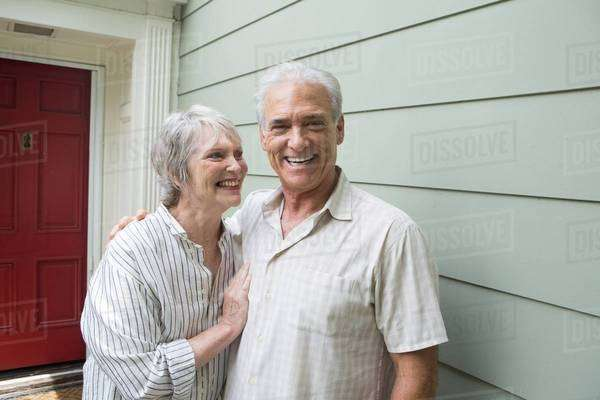 Senior couple smiling together outside house, portrait Royalty-free stock photo