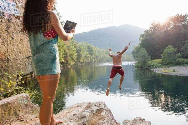 Woman photographing boyfriend jumping from rock ledge, Hamburg, Pennsylvania, USA Royalty-free stock photo