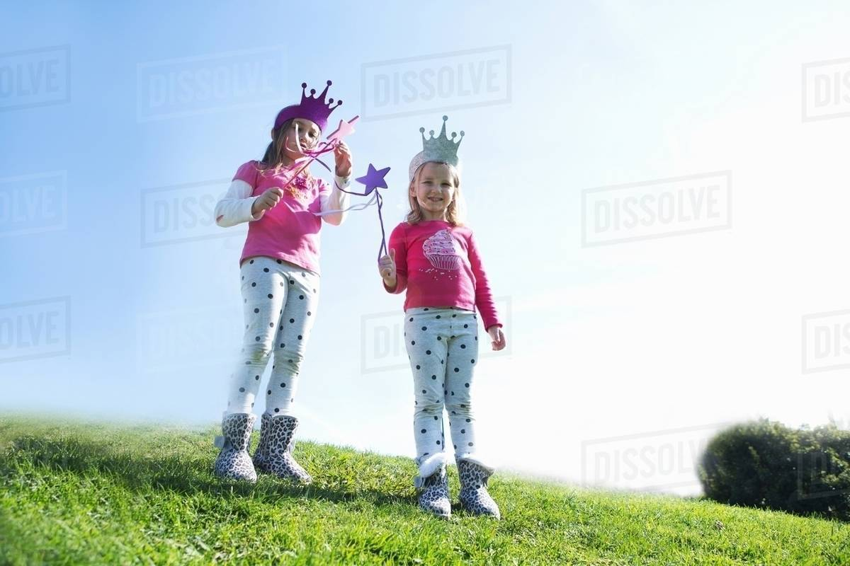 Two young sisters dressed up as fairies standing on hill Royalty-free stock photo