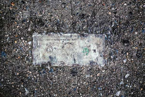Still life of deteriorating one dollar bill on wet pavement Royalty-free stock photo