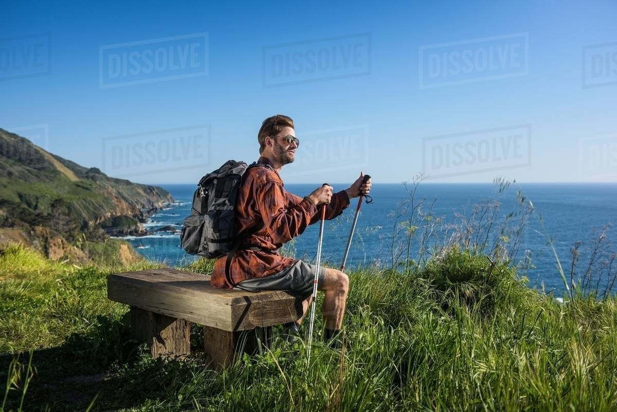 Young Male Hiker Looking Out From Cliff Top Bench Sur California Usa