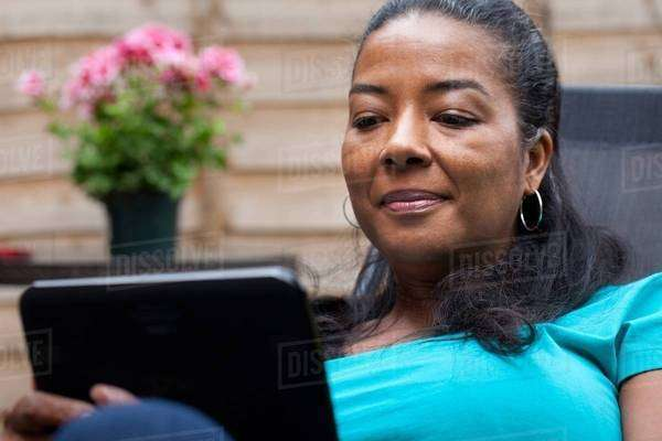 Mature woman sitting in garden reading digital tablet Royalty-free stock photo