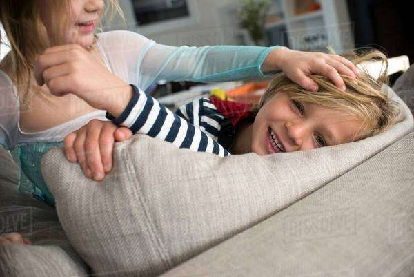 Children in costumes playing on sofa Royalty-free stock photo
