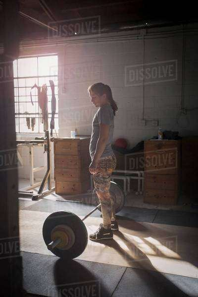 Woman preparing to lift barbell in gym Royalty-free stock photo