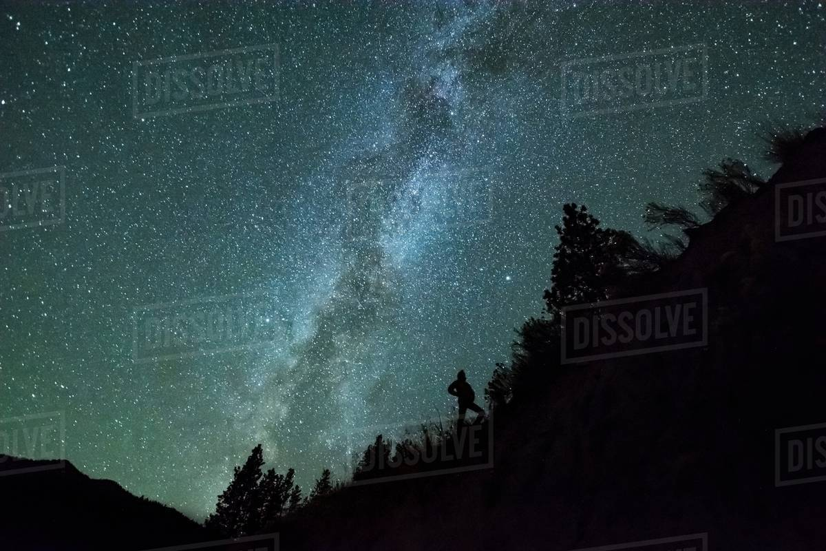 Man silhouetted against night sky and milky way in mountain forest, Penticton, British Columbia, Canada Royalty-free stock photo