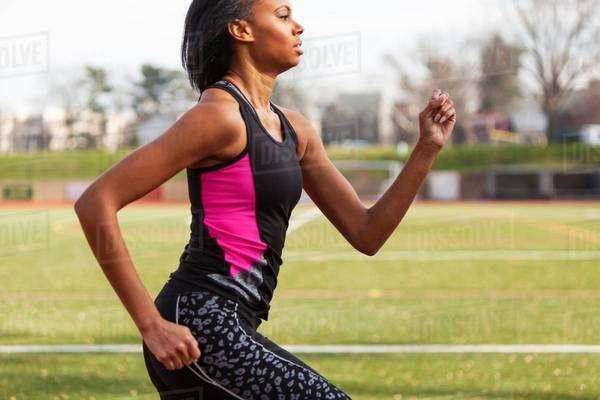 Young woman running on race track Royalty-free stock photo