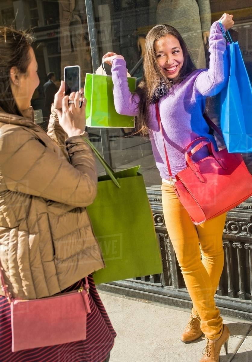 Young female adult twins in city taking smartphone photographs with shopping bags Royalty-free stock photo
