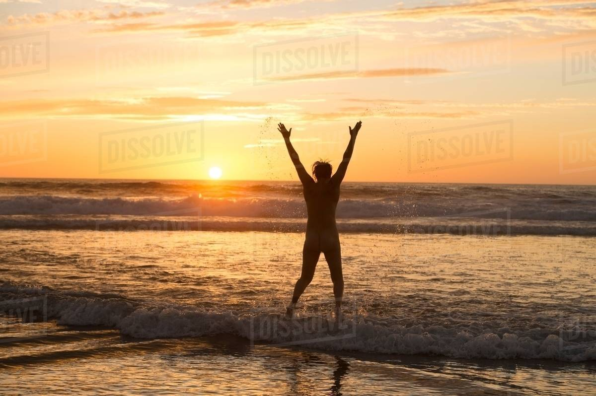 Rear view of mid adult nude womans silhouette standing in ocean at sunset,  arms raised