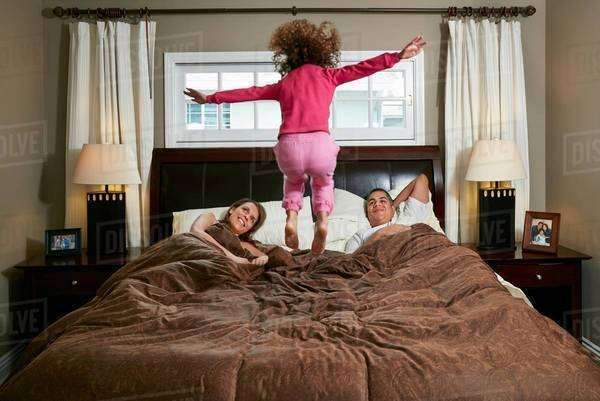 Rear view of girl in mid air jumping on parents bed Royalty-free stock photo