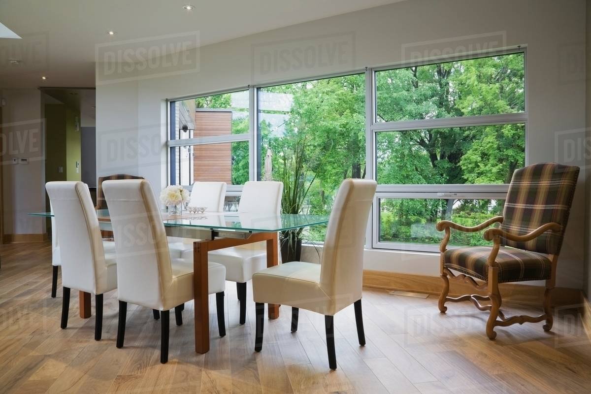 Glass Dining Table And Leather Chairs In Front Of Large Window In Modern Dining Room Stock Photo Dissolve