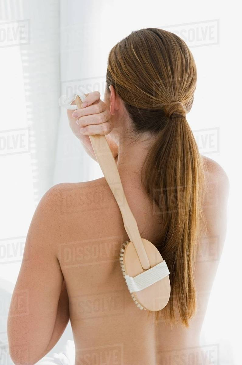 Young woman exfoliating her back Royalty-free stock photo