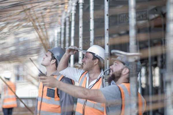 Site manager and builders looking up at steel rod structure on  construction site Royalty-free stock photo