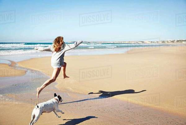 Mature woman and dog leaping over water on beach, Conil de la Frontera, Spain Royalty-free stock photo