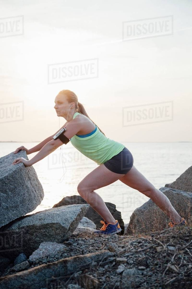 side view of woman wearing activity tracker stretching on rocks