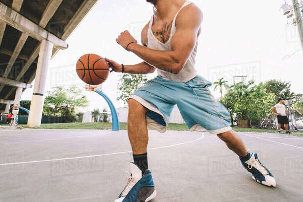 Cropped view of man on basketball court running, bouncing basketball Royalty-free stock photo