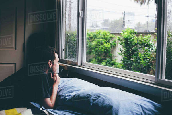 Man lying on bed staring through window at rain Royalty-free stock photo