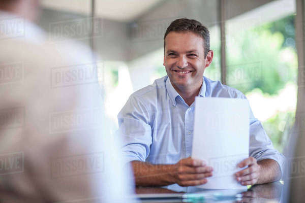 Happy male designer with paperwork at design office desk Royalty-free stock photo