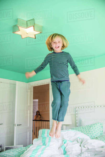 Boy wearing pyjamas jumping on bed smiling Royalty-free stock photo