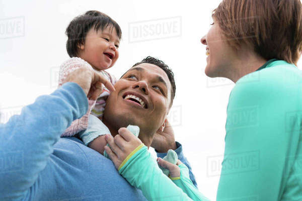Couple playing piggyback ride with baby in park Royalty-free stock photo