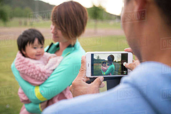 Father taking photograph of mother and baby in park Royalty-free stock photo
