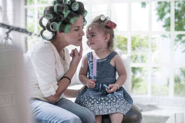 Mother in hair rollers pointing cheek to daughter Royalty-free stock photo