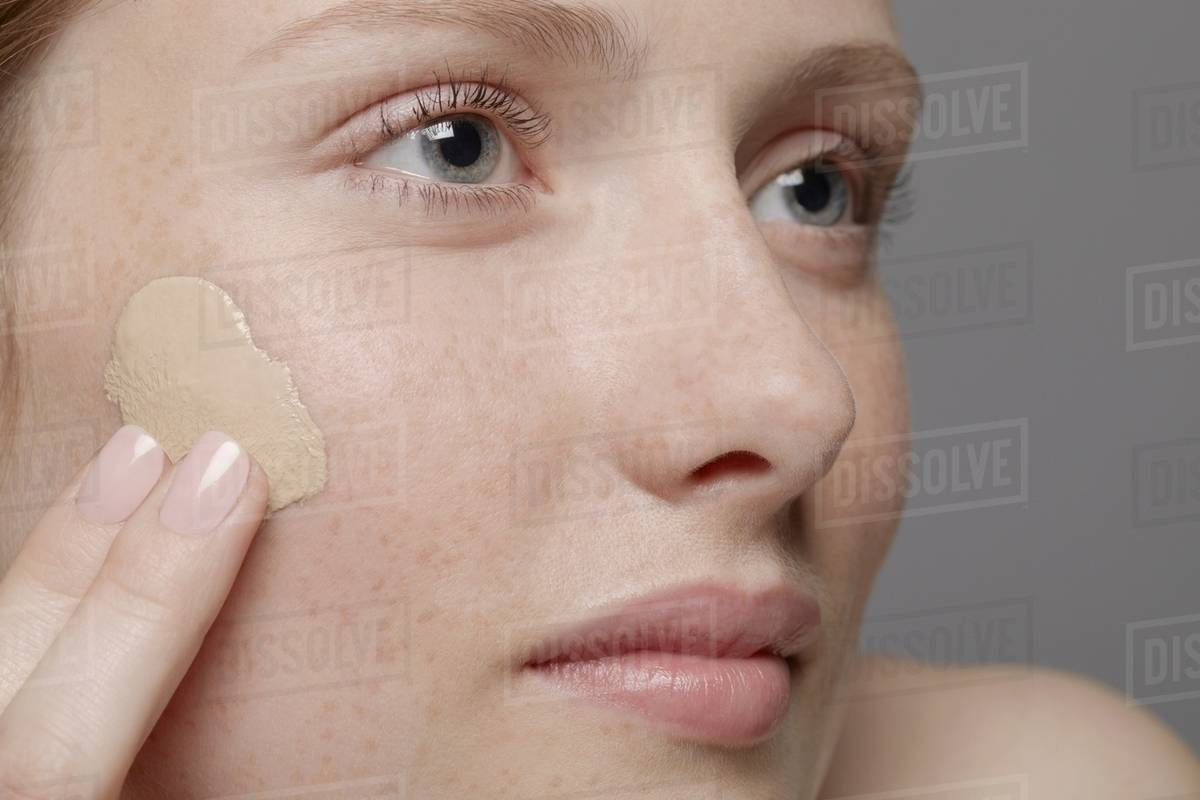 Close Up Of Part Young Womans Face Applying Concealer Stock