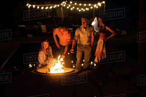 Mature adult couples  toasting marshmallows on patio fire at night Royalty-free stock photo