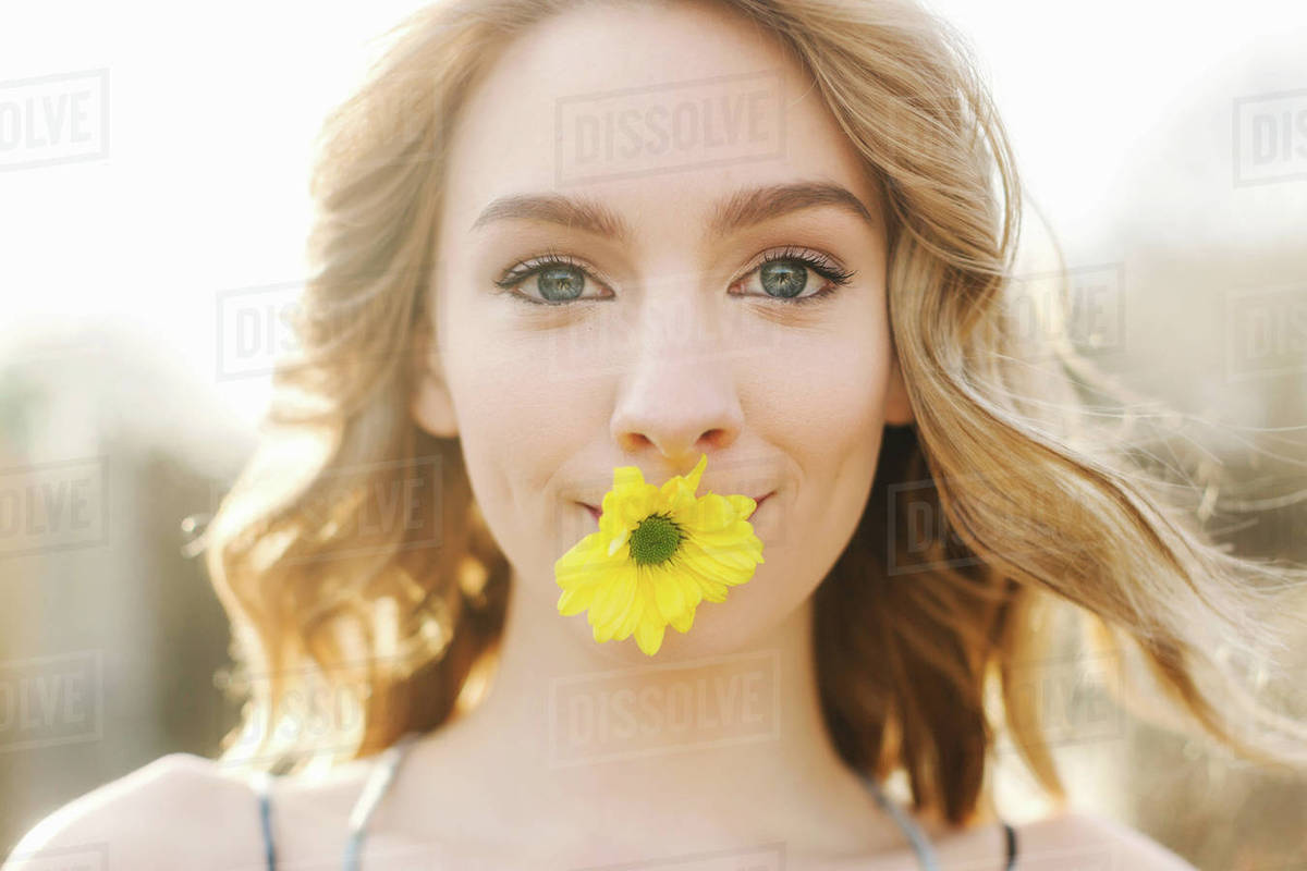 Portrait Of Young Woman With Yellow Flower In Mouth Stock Photo