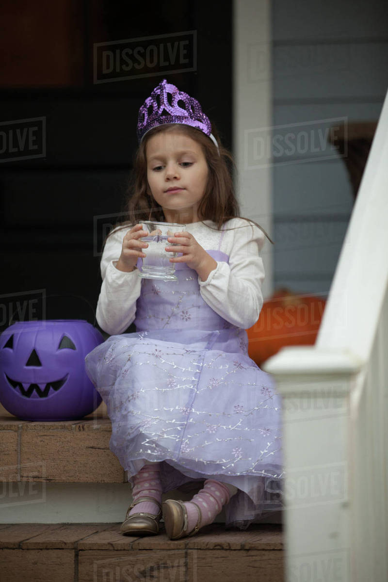 Girl trick or treating in fairy costume sitting on stairway drinking lemonade Royalty-free stock photo