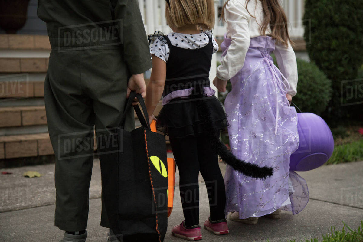 Boy and sisters trick or treating waiting at porch stairway Royalty-free stock photo
