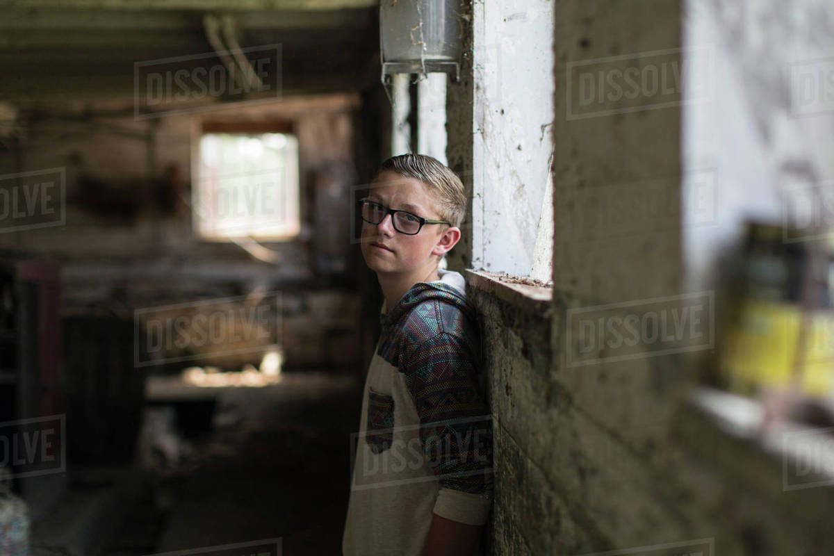 31e4cb300da Portrait of teenage boy wearing tinted eyeglasses leaning against shed wall