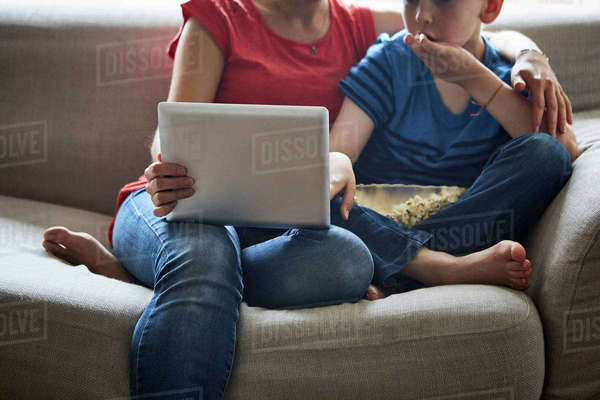 Cropped view of mother and son on sofa with popcorn using smartphone Royalty-free stock photo