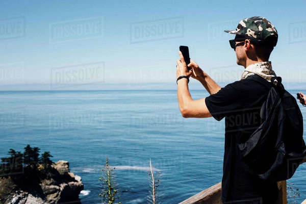 Man photographing seascape on smartphone, Big Sur, California, USA Royalty-free stock photo