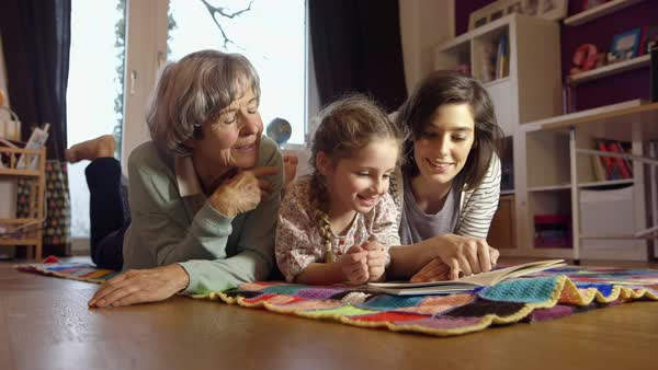 MS Girl (4-5) lying on floor with mother and grandmother reading book / Munich, Bavaria, Germany Royalty-free stock video