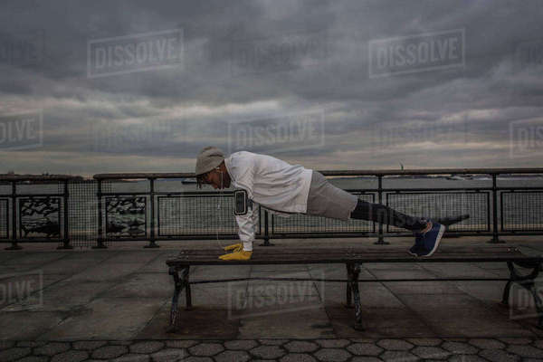 Young man bench push up training on riverside at dawn Royalty-free stock photo