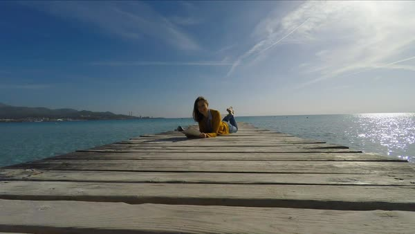 Wide shot of medium point-of-view shot of woman lying on wooden pier and reading Royalty-free stock video