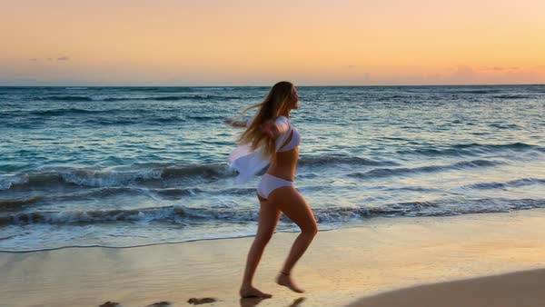 Wide shot of tilt shot young woman walking and spinning around on beach Royalty-free stock video