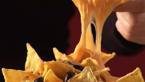 Hand taking nacho with melted cheese from plate Royalty-free stock video