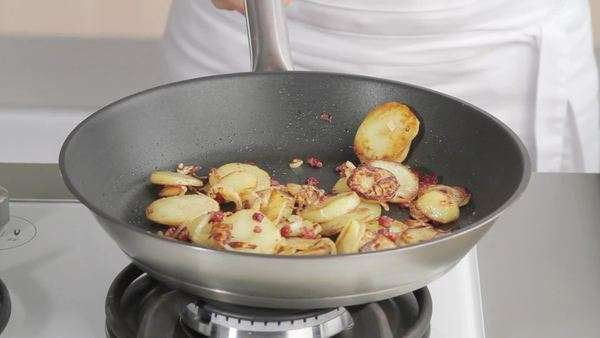 Tossing sauté potatoes with lardons in a frying pan Royalty-free stock video