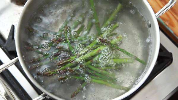 Green asparagus being added to a pot of boiling water Royalty-free stock video