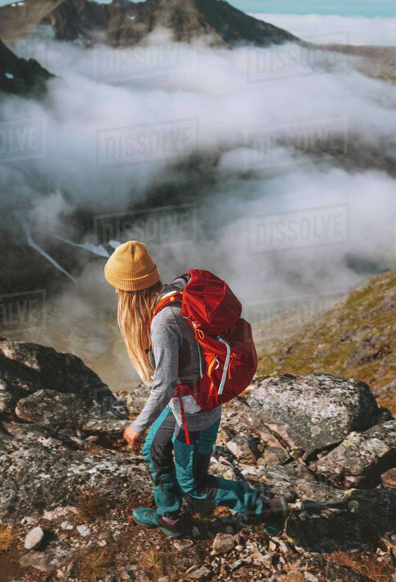 Woman hiking in mountains with red backpack travel trail running activity summer vacations healthy lifestyle outdoor adventure solo trekking in Norway  Royalty-free stock photo