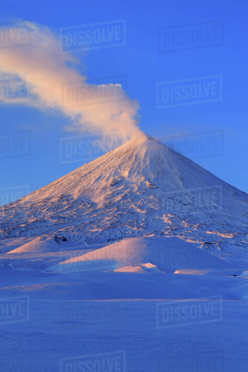 Picturesque winter volcanic landscape of Kamchatka Peninsula: view of eruption active Klyuchevskoy Volcano at sunrise. Eurasia, Russia, Far East, Kamchatsky Region, Klyuchevskaya Group of Volcanoes. Royalty-free stock photo