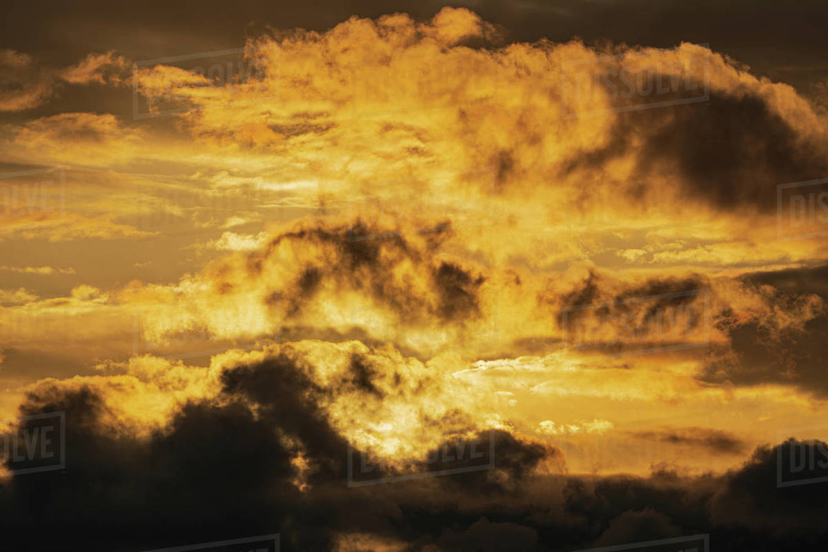 Dramatic clouds illuminated rising of sun in sky to change weather. Natural meteorology background. Soft focus, blurred motion. Heavenly landscape image ready for design, replace sky in photo editor. Royalty-free stock photo