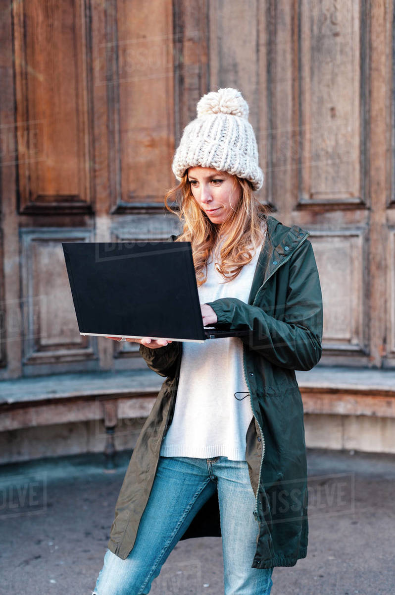 Creative entrepreneur woman working on laptop wearing casual clothes and a hat standing at urban park on sunny afternoon in London, UK Royalty-free stock photo