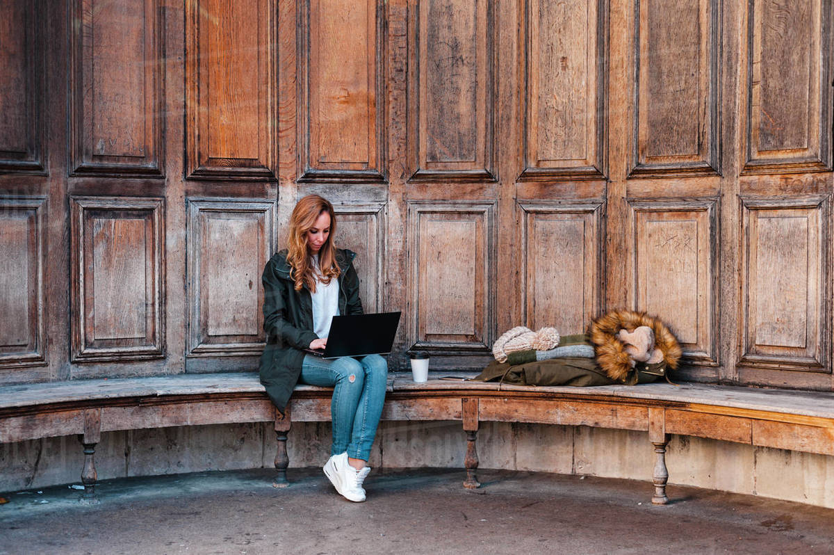 Creative entrepreneur working on laptop wearing casual clothes  seated at bench in urban park on sunny afternoon in London, UK Royalty-free stock photo